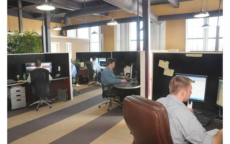 an office cubicle space with people at computer desks