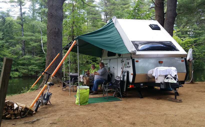 A Small Camper With A Small Tarp Overhanging People Sitting In Chairs ...