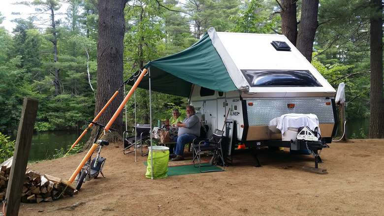 a small camper with a small tarp overhanging people sitting in chairs