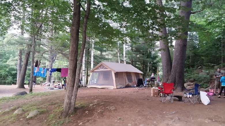 a campsite with a tent, chairs, a clothesline with towels, and people standing to one side