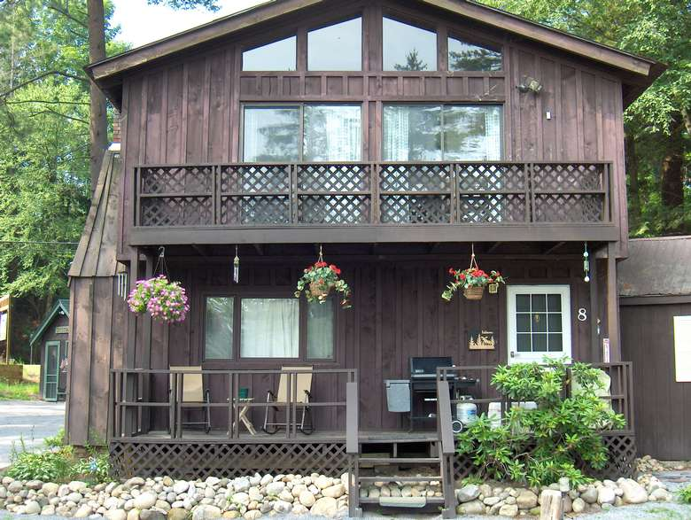 a large cabin with two stories, deck off second floor
