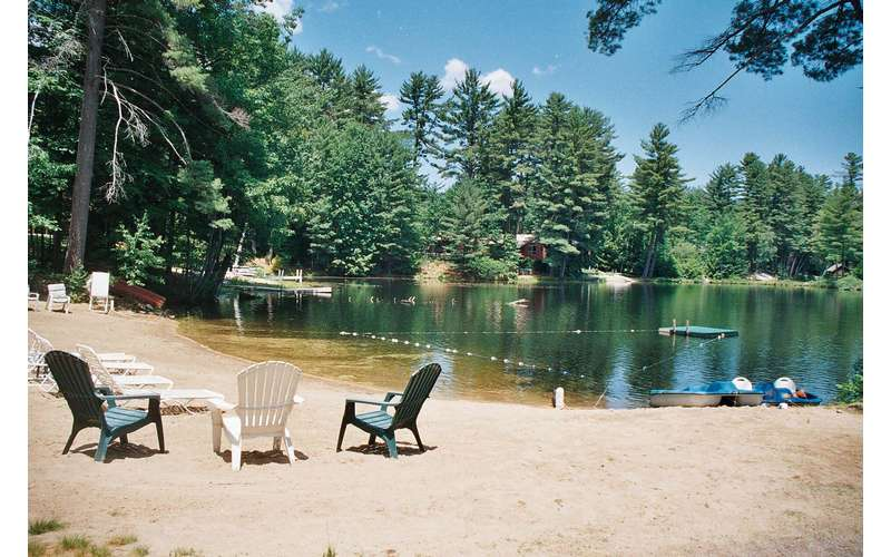 different view of beach with chairs, trees surrounding lake
