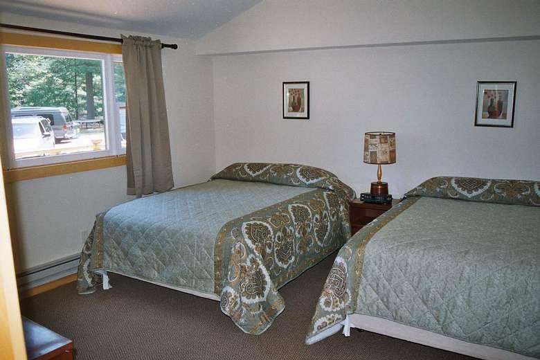 two beds in a bedroom, open window