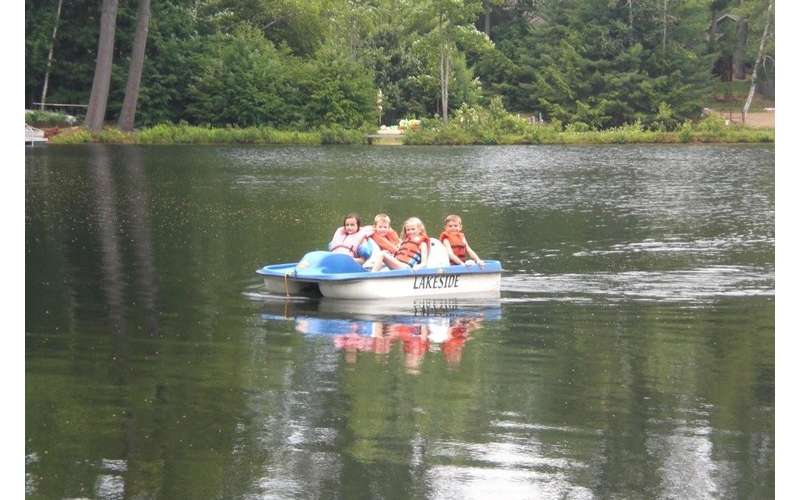 four kids in a small boat
