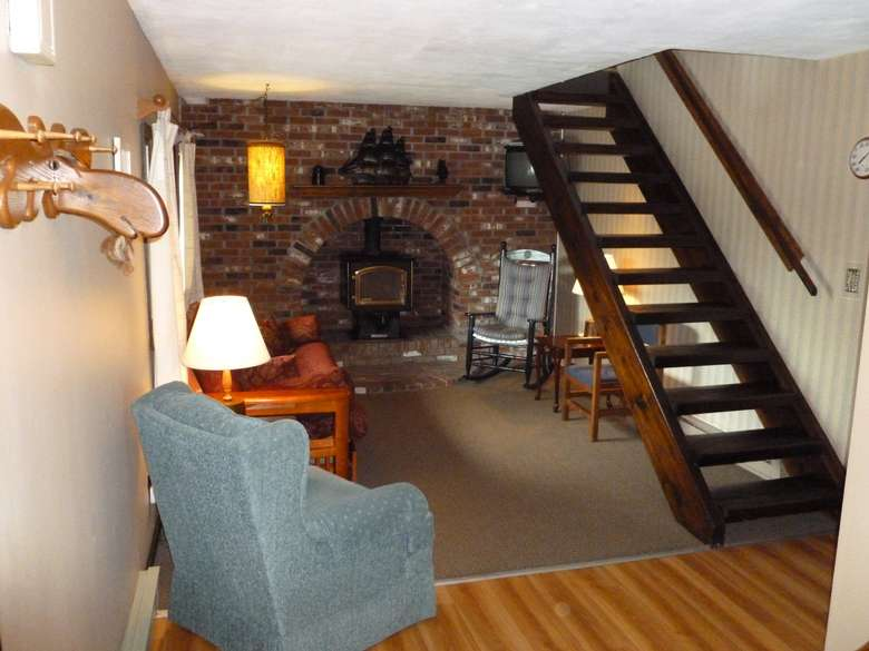 quaint wooden stairs in a cottage, there's a fireplace
