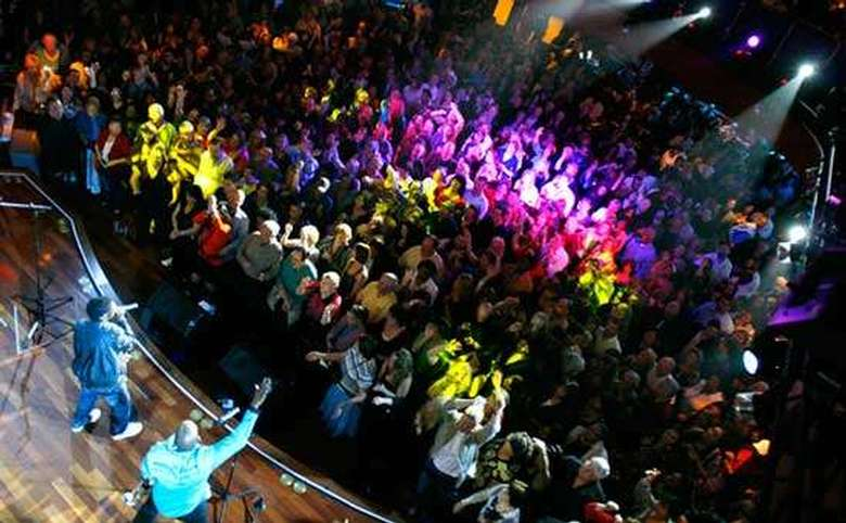 view from above of a band performing for a packed nightclub crowd