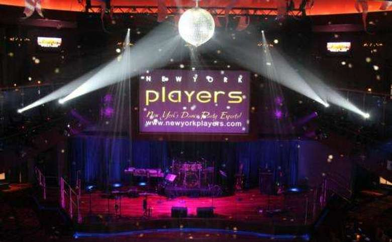 empty stage with a drum set in the back and the new york players logo projected onto a screen above it
