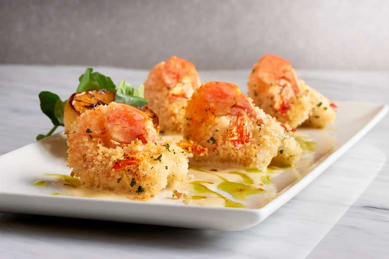 four crispy stuffed shrimp on a white plate