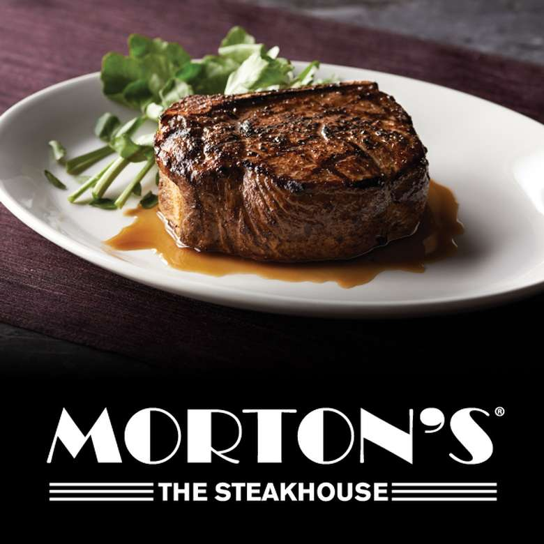 steak on a plate with brown sauce and the morton's logo