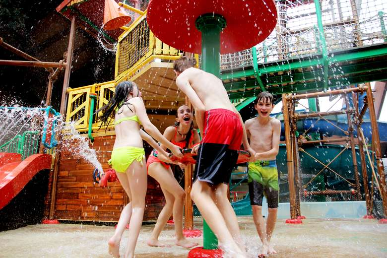 group of kids splashing around in an indoor waterpark
