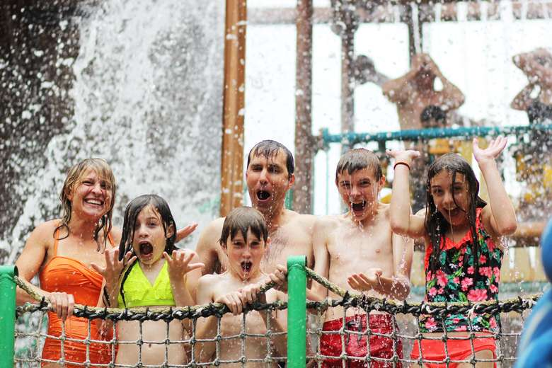 group of people getting sprayed in an indoor waterpark