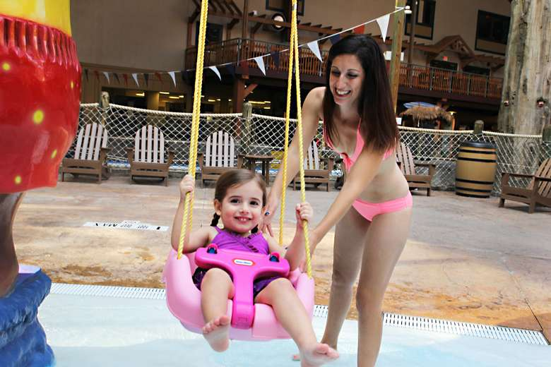 mother pushing her daughter on a swing in an indoor waterpark