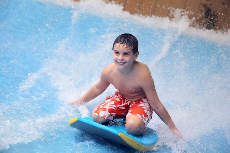 boy on a kneeboard in an indoor waterpark