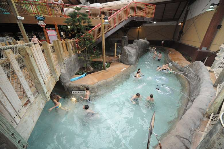 people floating on a lazy river in an indoor waterpark