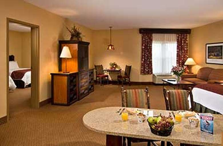 hotel suite with three beds, a seating area, and a kitchenette