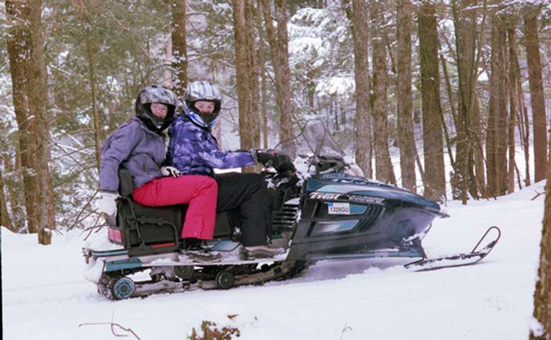 two people riding one snowmobile in the woods