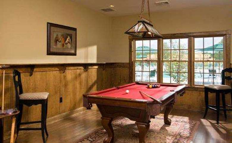 pool table with red felt set in front of large windows