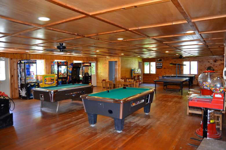 a game room with several pool tables, arcade games