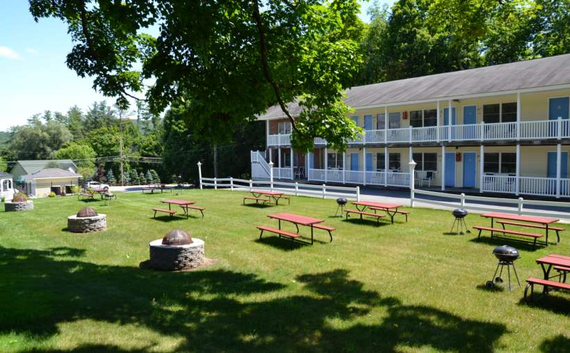 row of apartments or motels, picnic tables with grills on lawn