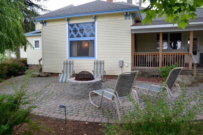 back of a cottage with a fire pit in the back and chairs