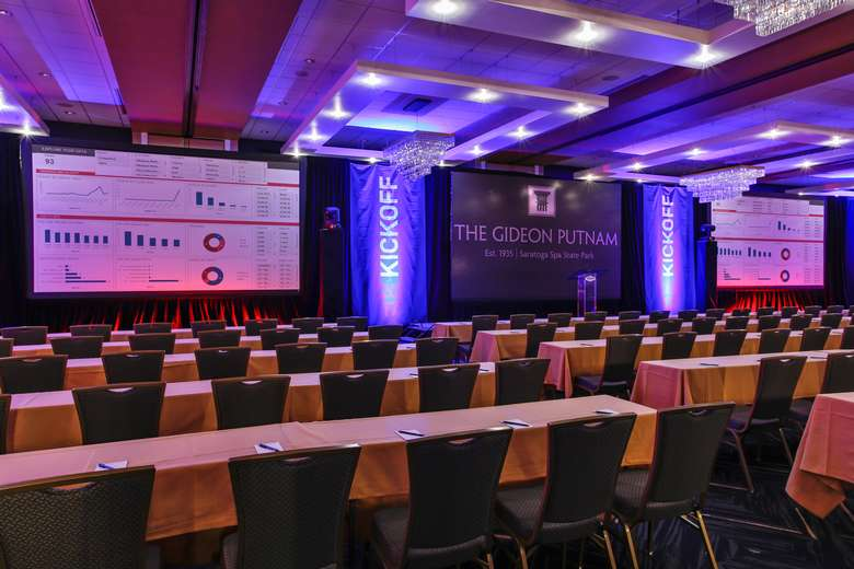 ballroom with long rectangular tables and two large projection screens set up for a conference or meeting