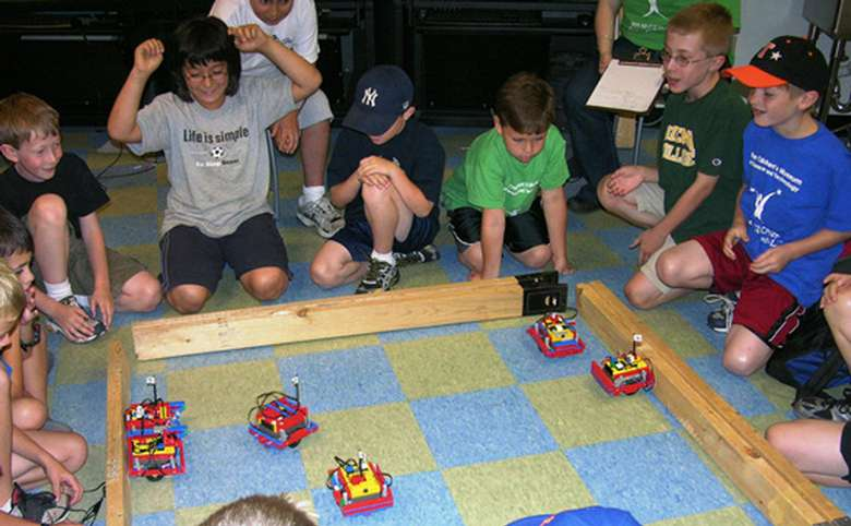 Group of kids watching robots within a rectangle