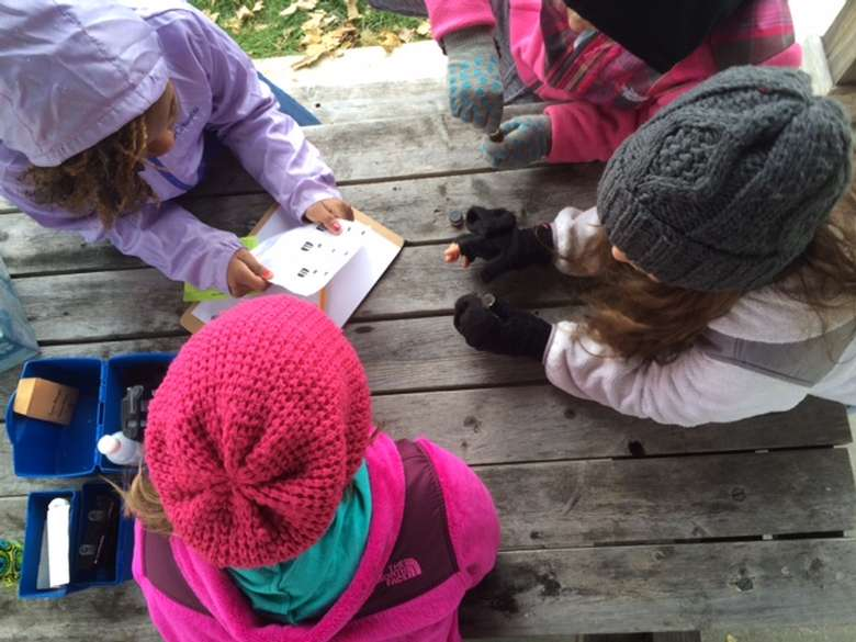 group of kids outside reading over a science activity