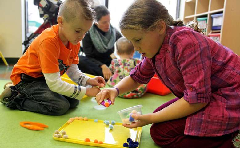Children sorting circular objects by color