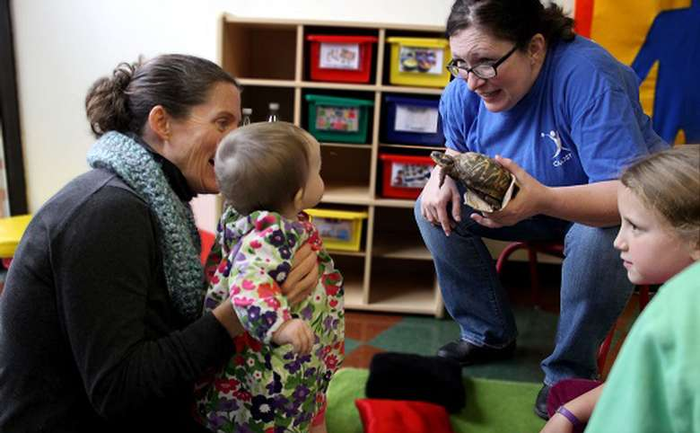 Employee holding a turtle and showing it to kids