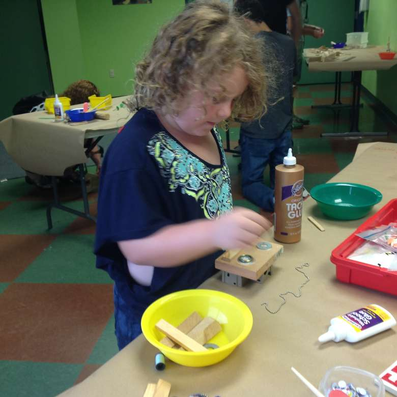 Girl glueing objects together