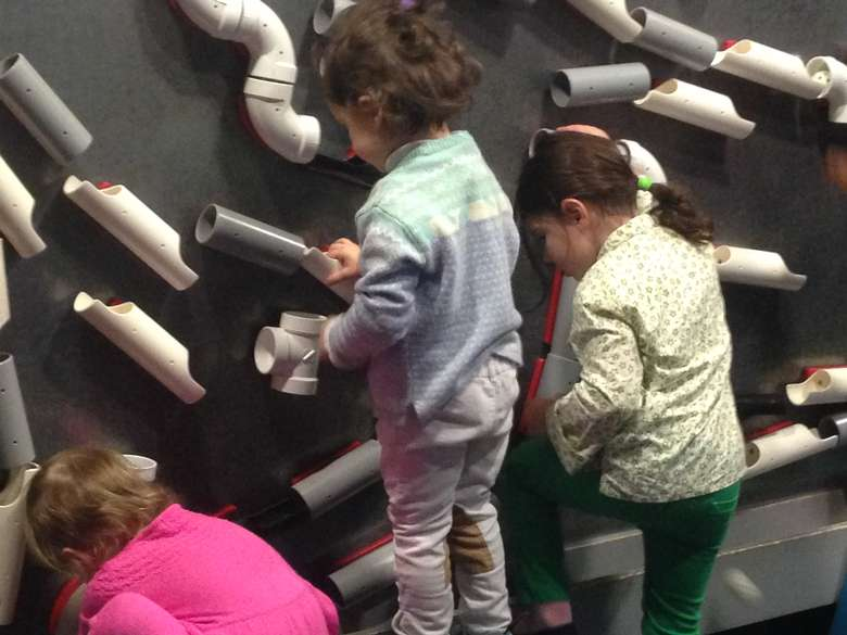 Kids playing with a wall of tubes that balls travel through
