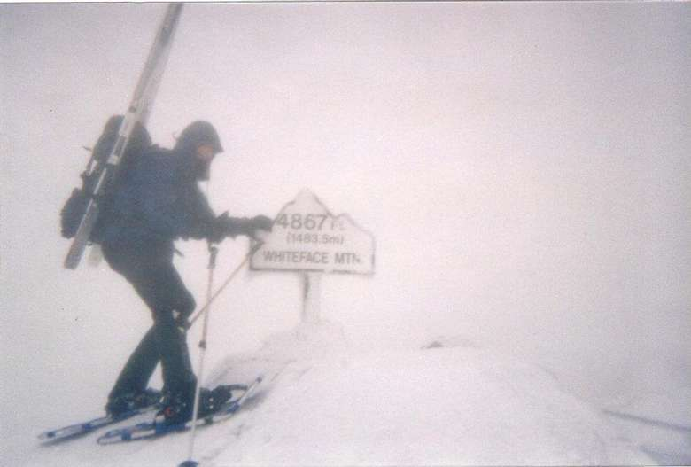 hiker standing at the summit of whiteface mountain in a snowstorm