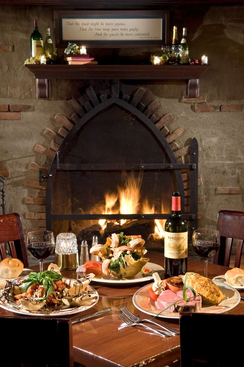 restaurant table in front of a fireplace with several plates of entrees