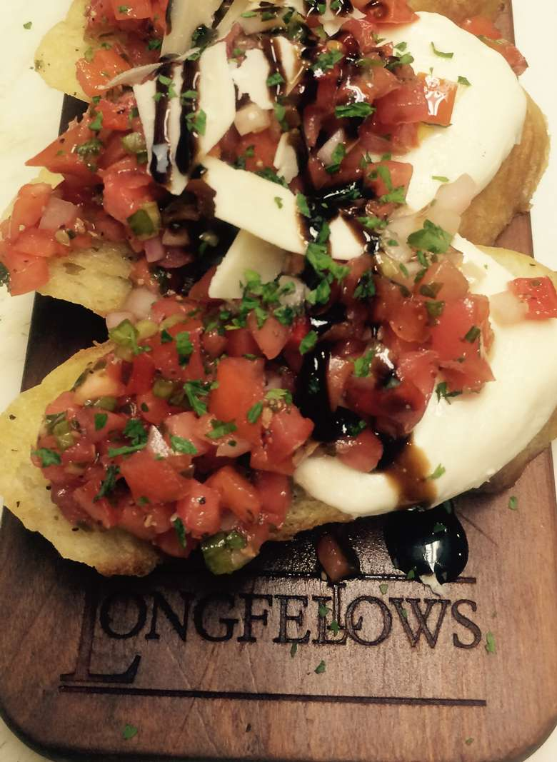 bruschetta on a cutting board with longfellows' logo stamped into it