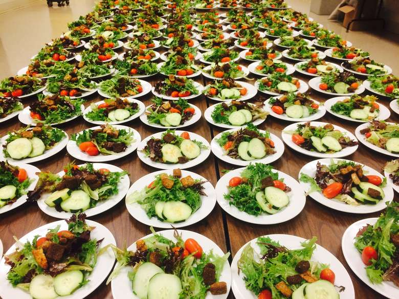dozens of salads prepped for a large event