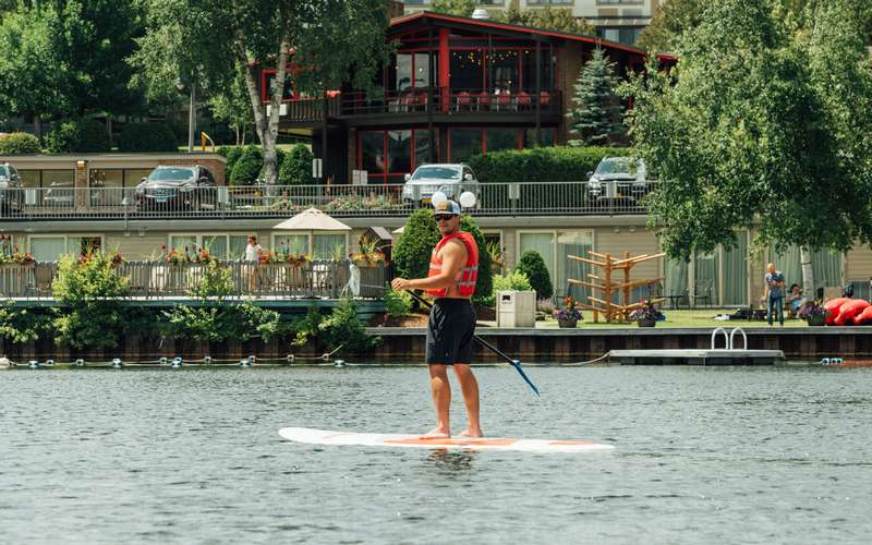 Man stand up paddleboarding on Mirror Lake.