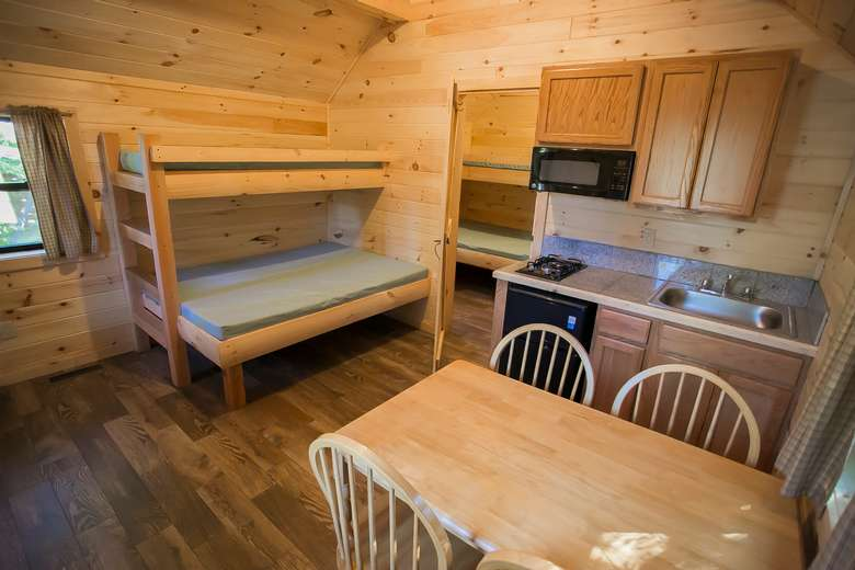 inside view of cottage showing eat-in efficiency kitchen and bunk beds