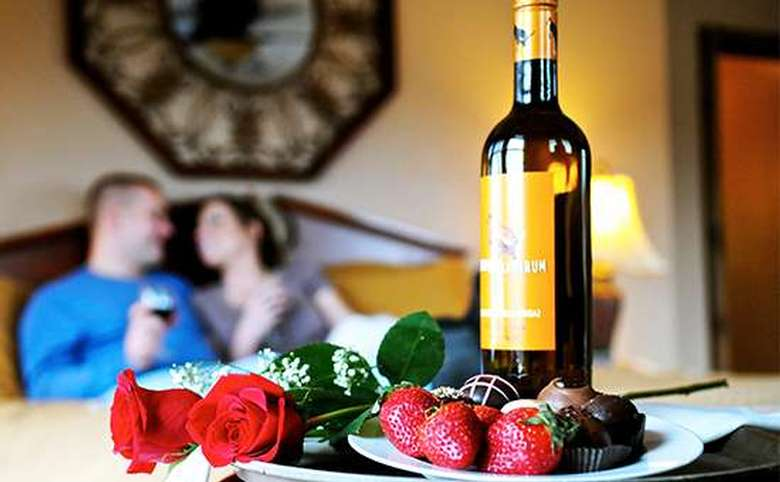 young couple relaxing in bed in background with bottle of wine, roses, strawberries and chocolates in foreground
