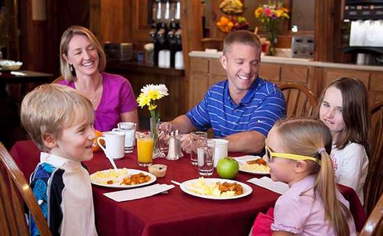 woman, man and three children eating breakfast and laughing