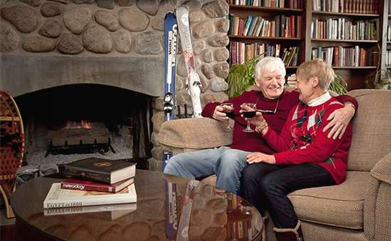 older couple relaxing on the couch in front of fire with two glasses of red wine and skis in the background