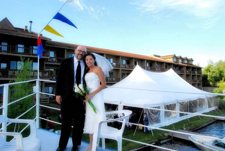 married couple standing on deck with reception tent in the background