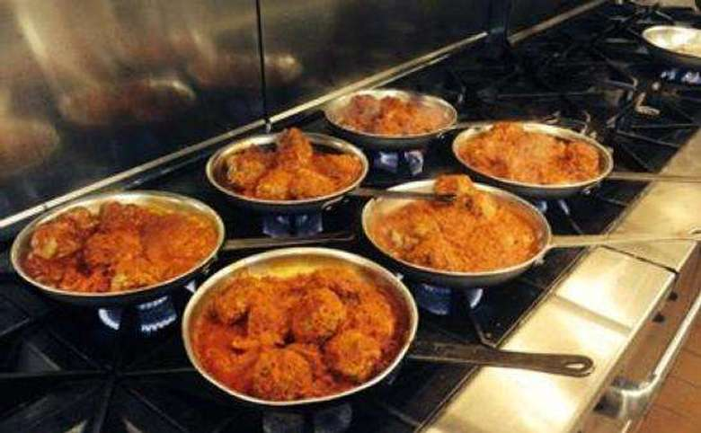 six skillets full of italian dishes on a commercial sized oven