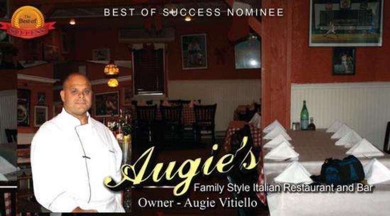 chef/owner augie standing inside his restaurant