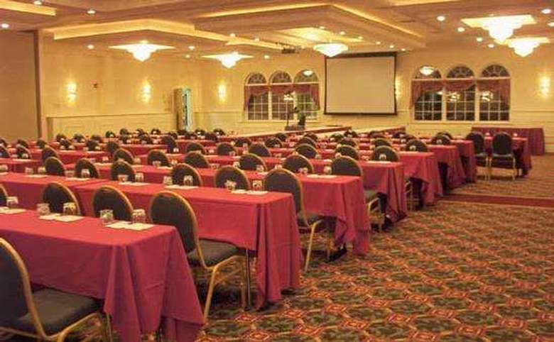 hotel ballroom with many long tables set up for a conference