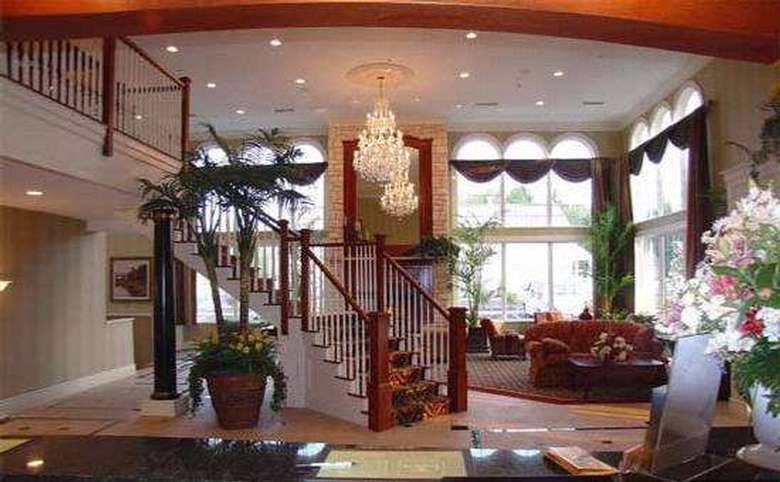 main lobby of a hotel with a large wooden staircase leading up to the second floor