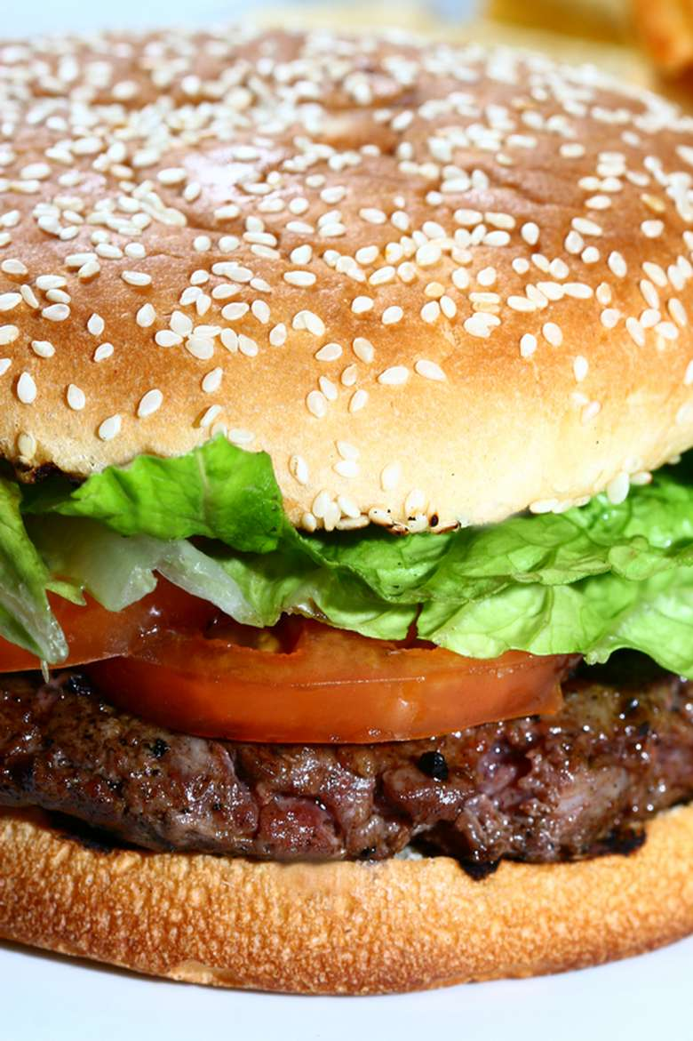 A hamburger on a sesame seed bun with tomato and lettuce