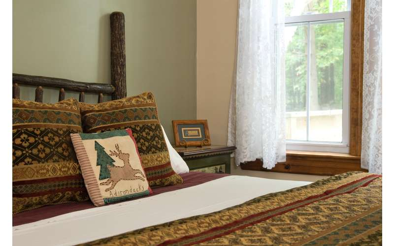 a bed with a pillow with a deer on it that says adirondacks
