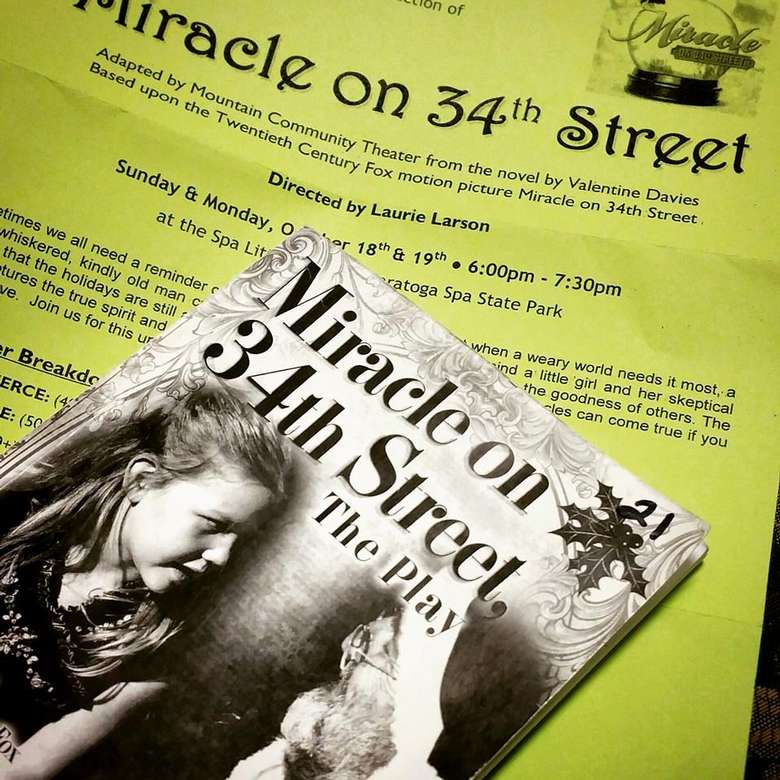 booklet that says miracle on 34th street the play with a lime green flyer about the play behind the booklet