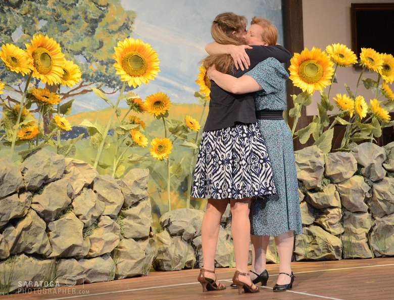 two actresses hugging on stage in front of a field of sunflowers