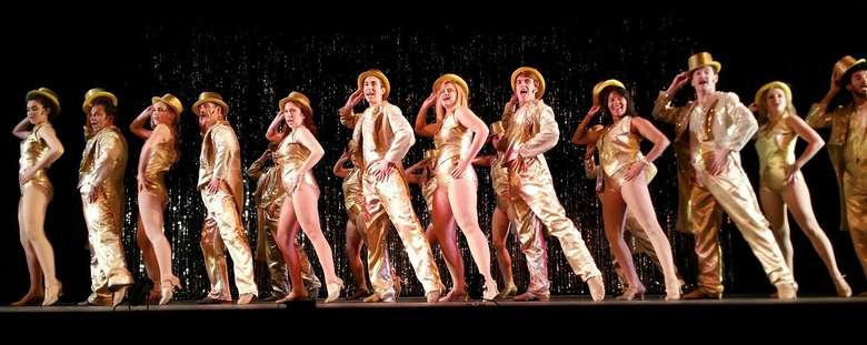 actors performing in a chorus line wearing gold vests, pants, leotards, and top hats